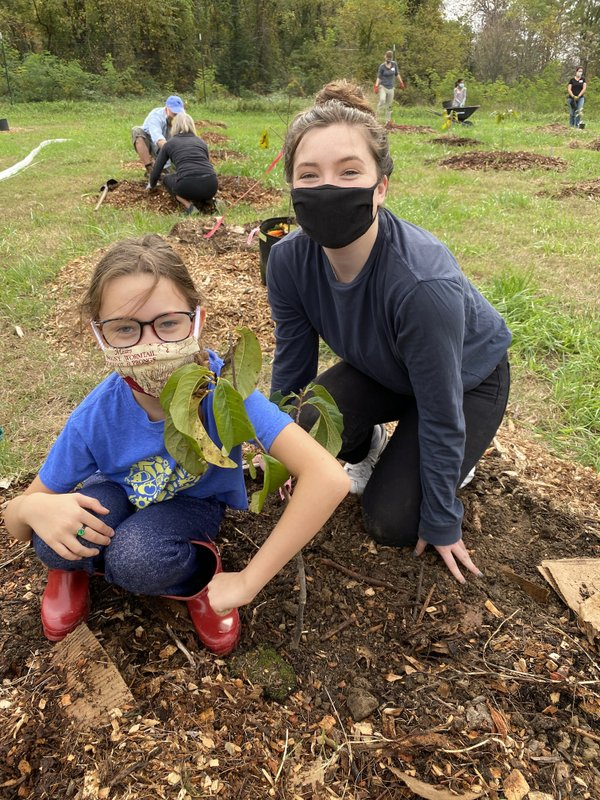 Participants help plant fruit trees Wednesday at Arcadia Farm.